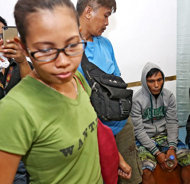 Jayme Jayson (seated right), suspect in the killing of Catmon police chief Senior Insp. Alexander Nuñez, is presented to the Provincial Prosecutor's Office. At left is Nuñez's wife PO3 Queen Bridgette Nuñez. (CDN PHOTO/JUNJIE MENDOZA).